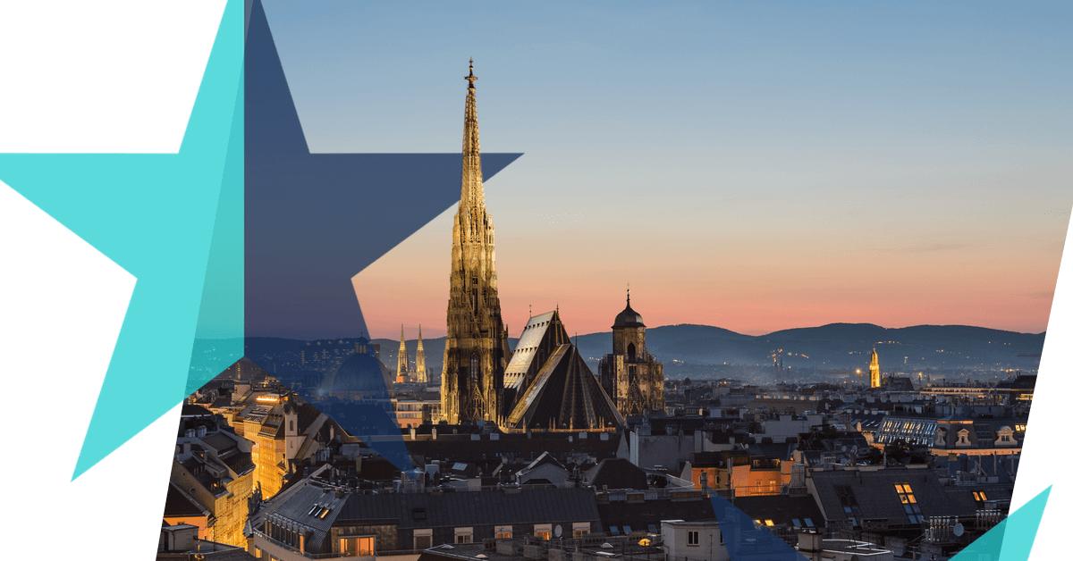 Blick über die Wiener Innenstadt. Die Spitze des Stephansdom erleuchtet vor einer hellrosa-blauen Abenddämmerung. Ein I-love-EU-Stern in Türkis und Dunkelblau hebt den Stephansdom hervor.