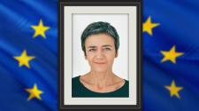 Bei der EU-Wahl 2019 entscheidet sich auch wer Kommissionspräsident_in wird. Auf dem Bild ist daher Margrethe Vestager in einem hochformatigen Bilderrahmen dargestellt. In den zwei äußeren Dritteln des Beitragsbildes ist eine verschwommene großflächig wehende EU-Flagge zu erkennen - sie bildet den Hintergrund.