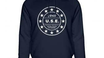 Der TURIN Hoodie von I love EU ist dunkelblau und hat vorne einen weißen Print in Kreisform mit dem EU-Sternenkreis und in der Mitte der Abkürzung U.S.E. die für Federal Republic United States of Europe steht. Diese Bezeichnung befindet sich ebenfalls darunter. Darüber steht die Jahreszahl 2045.