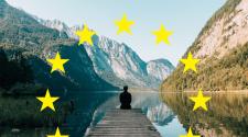 Das EU-Parlament hat die Mitgliedstaaten aufgefordert einen EU-Feiertag am 9. Mai einzuführen. Das Bild zeigt einen jungen Mann sitzend am Steg des Königssees. Im Hintergrund sind Berge zu sehen. Rund um den sitzenden Mann sind die kreisförmig angeordneten gelben Sterne der EU-Flagge zu sehen.
