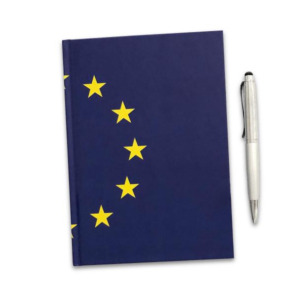Das I love EU Notizbuch Bruxelles ist DIN A5 hochformat und dunkelblau. Der gelbe EU-Sternenkreis geht über den Bug und reicht je bis zur Mitte der Vorder- und Rückseite. Rechts daneben liegt ein silberfarbiger Kugelschreiber der in etwa ein Drittel kleiner ist als die Längsseite des EU Notizbuch.