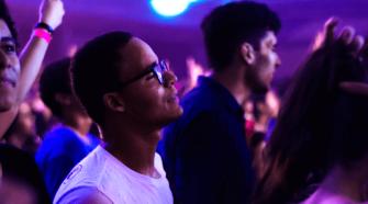 Bei der UNITE EU Party Vienna gibt es die besten Pop Hits aus ganz Europa. Auf dem Bild tanzt ein junger Mann mit geschlossenen Augen in einer Menschenmenge. Die Lichtstimmung ist warm und in Violetttönen.