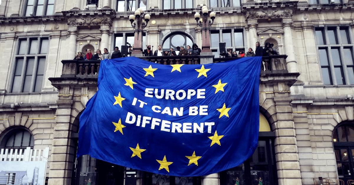 """Mehrere Person entfalten auf einem Balkon eines historischen Gebäudes eine mehrere Meter große EU-Flagge auf der steht """"Europe it can be different"""". Anlass dafür war das European Balcony Project."""