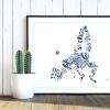 Valletta Print EU 59x42 weiß invert blau I love EU. Die Namen der Mitgliedstaaten stehen in Landessprache und Form des Landes in blau auf weißem Hintergrund in einem schlichten schwarz-weißen Bilderrahmen vor weißer Holzwand auf einem Holzboden stehend und an die Wand lehnend. Davor steht ein weißer Blumentopf mit zwei kleinen Kakteen drinnen.